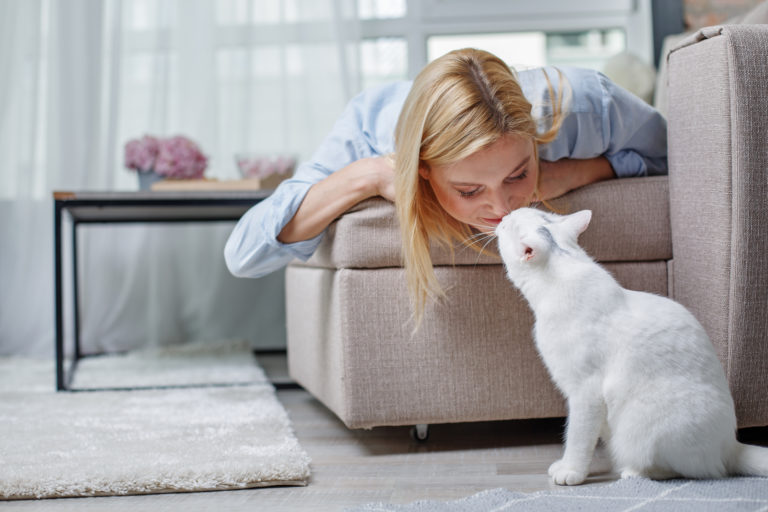 Woman cuddling with her indoor cat